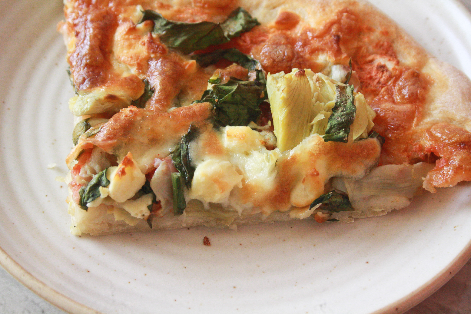 A chewy, deeply flavoured pizza crust topped with a simple tomato sauce, spinach and artichokes, plus lots of cheese!