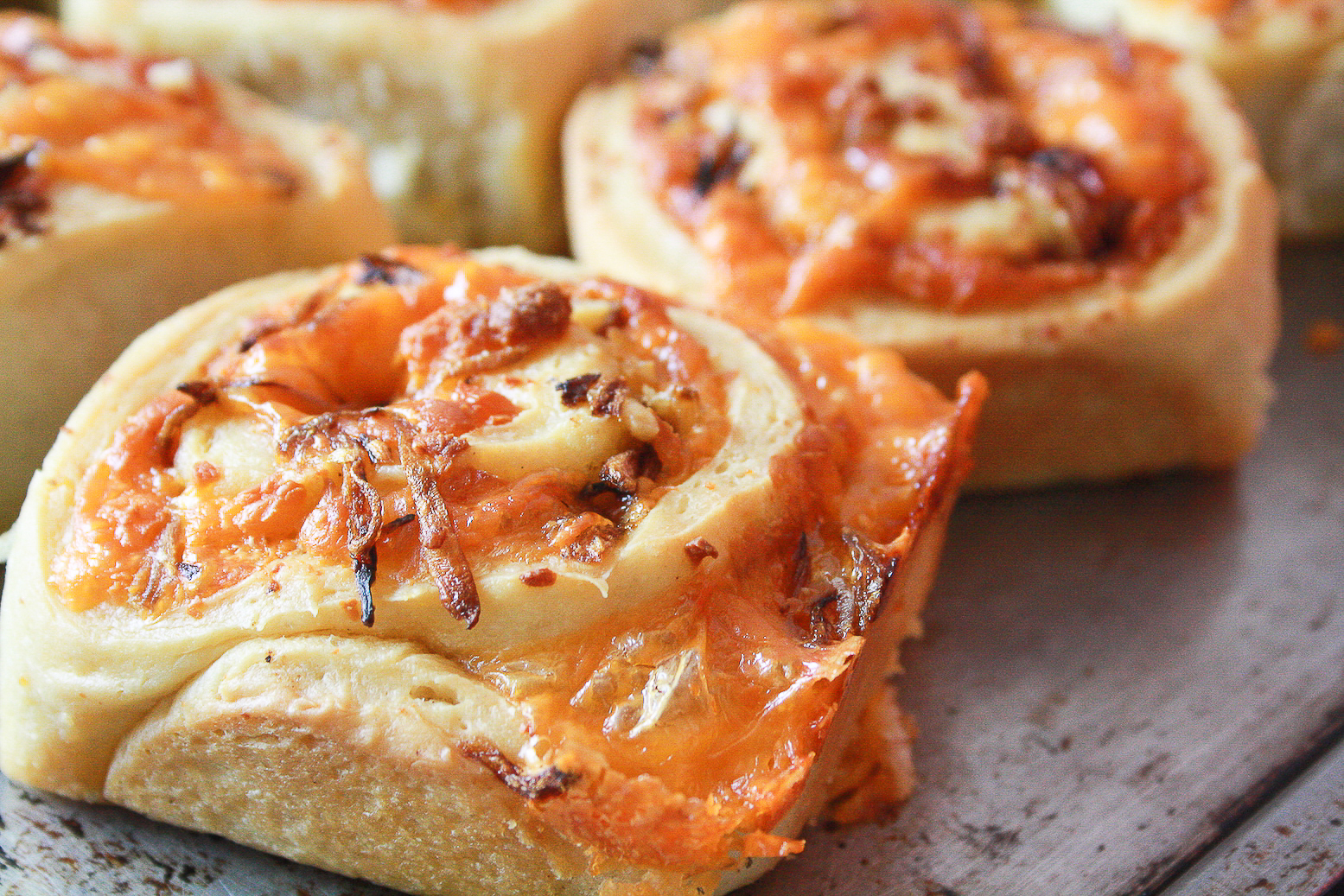 Soft and fluffy savoury rolls filled with orange cheddar and caramelised onions!