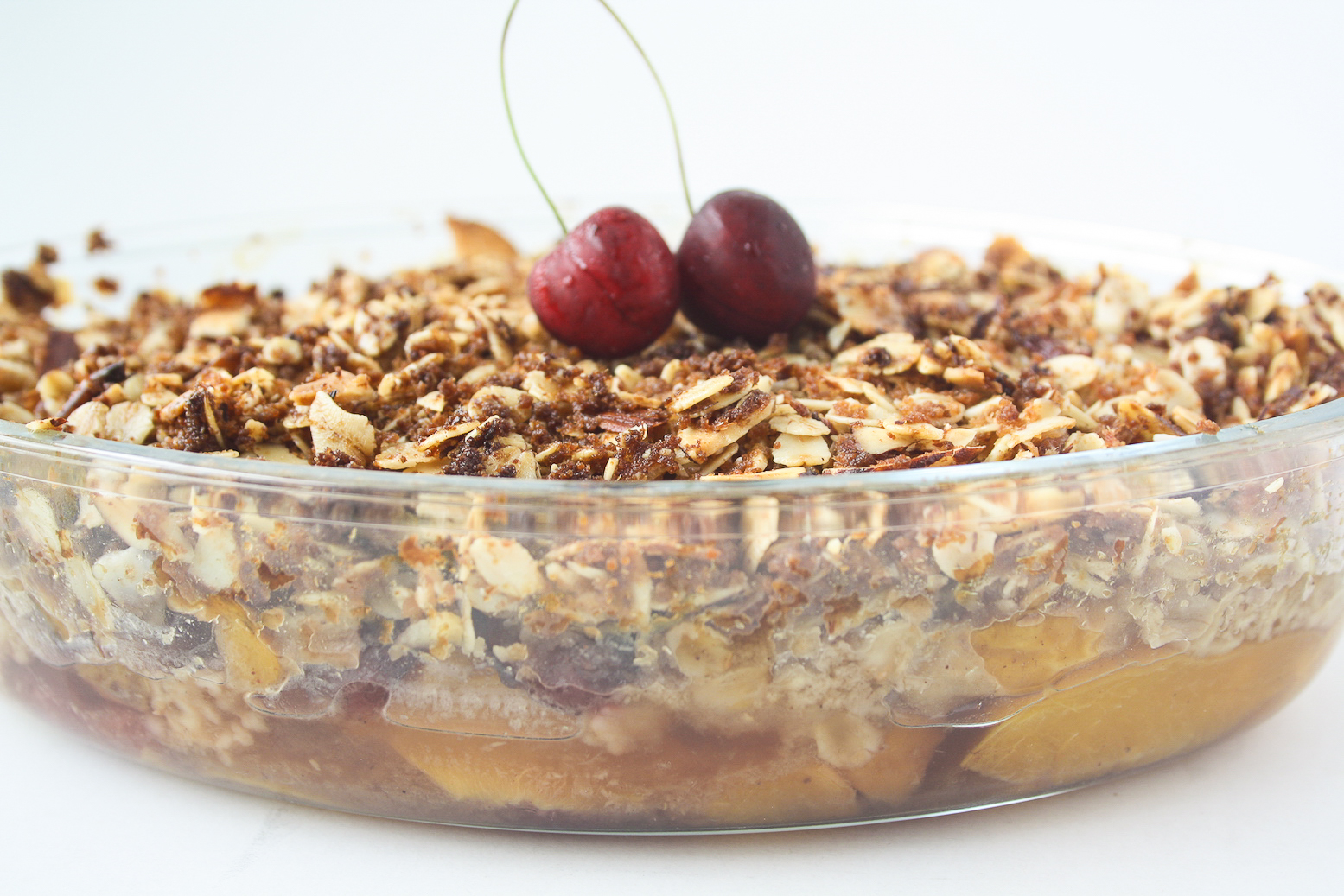 Inspiring Vegan Dishes That Will Taste You This Season-Fresh peaches and cherries with a delicious coconut oat topping make this vegan, gluten-free crisp the perfect summer dessert!