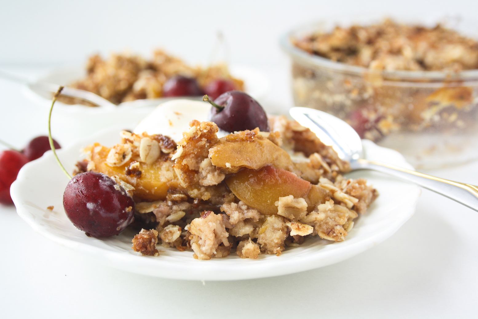 Fresh peaches and cherries with a delicious coconut oat topping make this vegan, gluten-free crisp the perfect summer dessert!