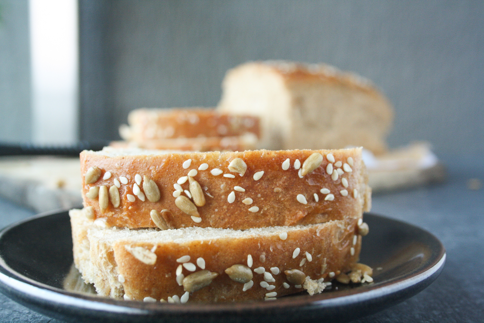 Soft and chewy homemade rye bread topped with sesame and sunflower seeds.